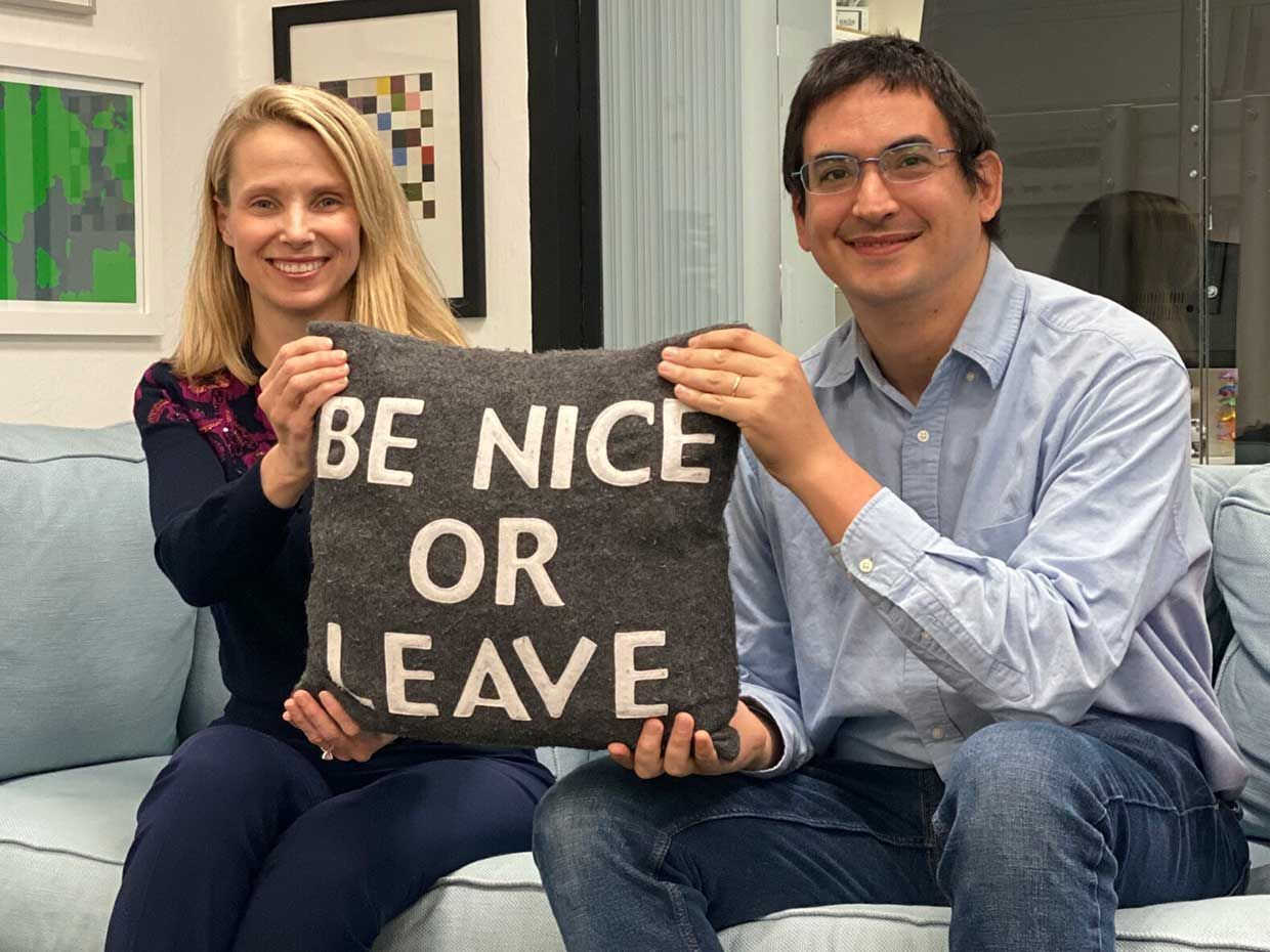 """Sunshine founders Marissa Mayer (left) and Enrique Munoz Torres hold a pillow that says """"Be nice or leave""""."""