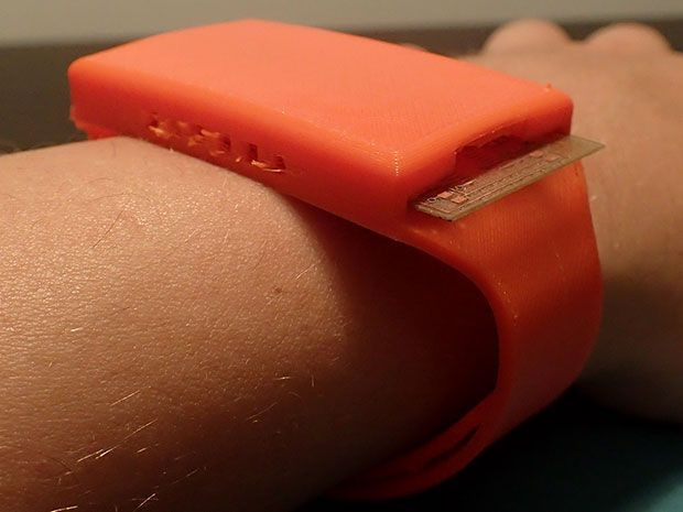 """The """"paper watch"""" is an orange wristband with electronic sensors on the underside."""
