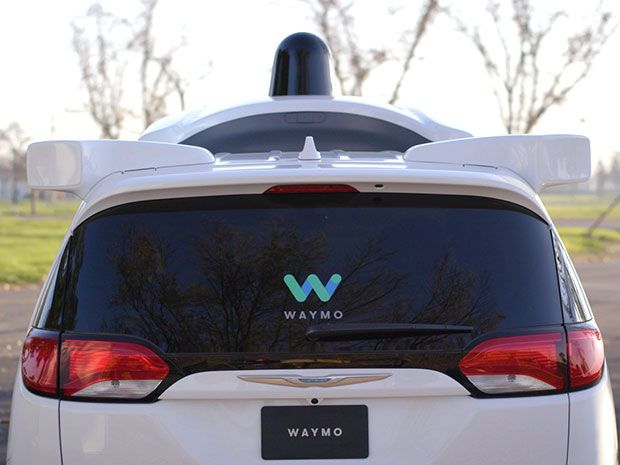 """The rear end of a white car with a black knob on top and sign that says """"Waymo"""" on the rear windshield"""
