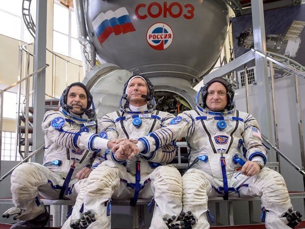 Three men sit in space suits in front of a metal capsule