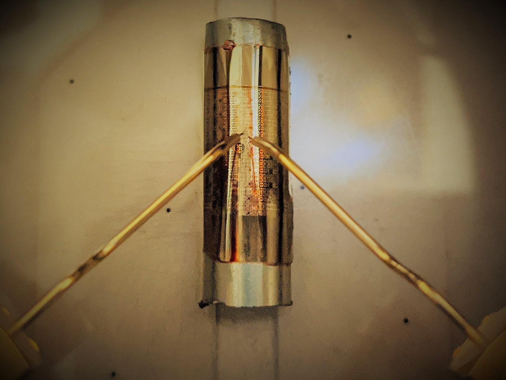 Two gold metallic probes hover over a silverish cyindrical shape, on which lies a golden shape that bends to the cylinder, and has golden and brown etchings on it.