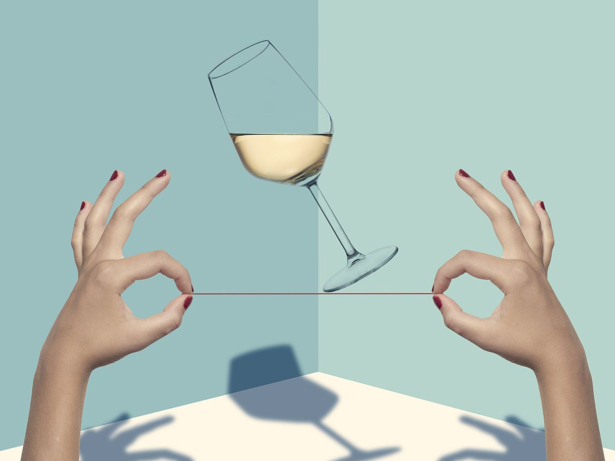 Two hands hold a string tightrope for a tipping glass of wine.