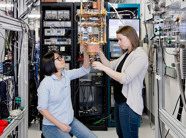 Two women surrounded by computing equipment study a device made from tubes and wires