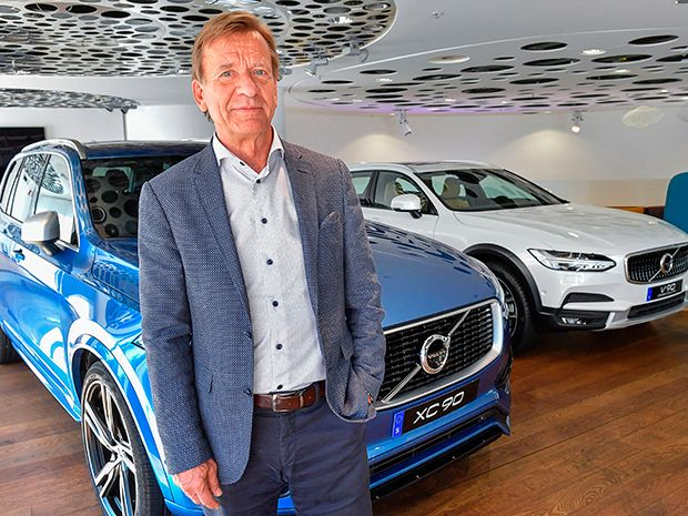 Volvo Cars CEO Hakan Samuelsson standing in front of a blue Volvo car and a white Volvo car