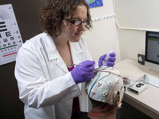 Woman fixing EEG electrodes to another woman's scalp