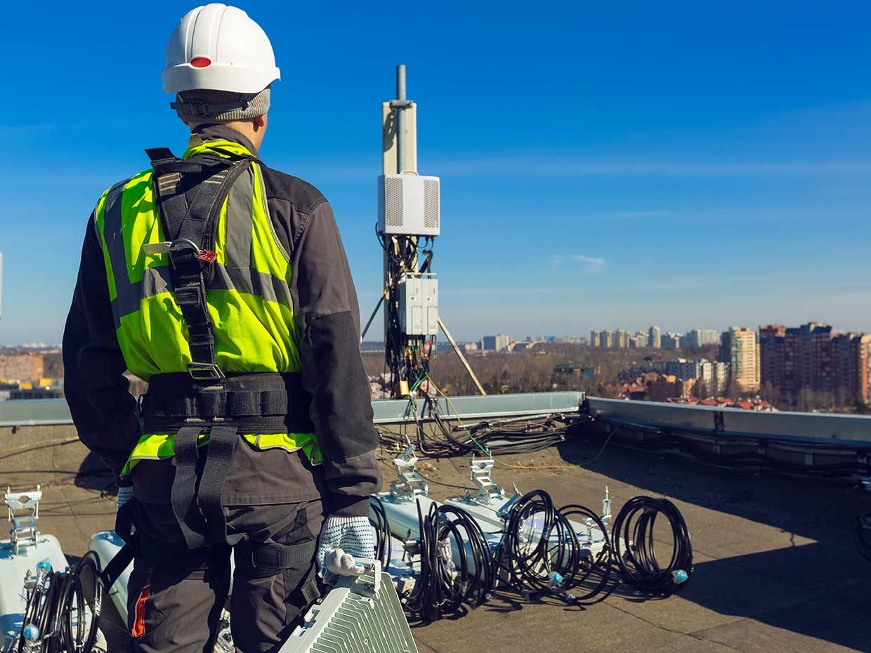 worker on a roof looking at wireless equipment