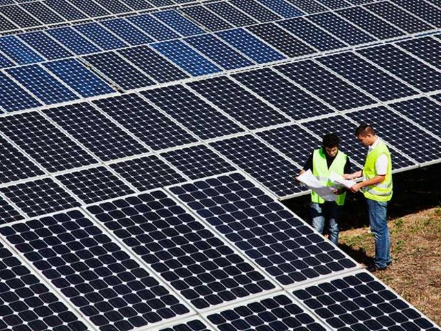 workers looking at solar panels